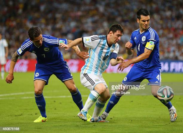 Lionel Messi of Argentina controls the ball against Muhamed Besic and Emir Spahic of Bosnia and Herzegovina during the 2014 FIFA World Cup Brazil...