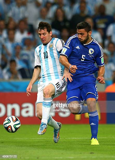 Lionel Messi of Argentina controls the ball against Sead Kolasinac of Bosnia and Herzegovina during the 2014 FIFA World Cup Brazil Group F match...