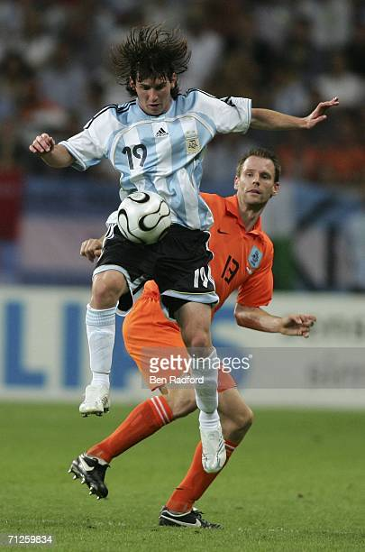Lionel Messi of Argentina controls the ball as Andre Ooijer of the Netherlands closes in during the FIFA World Cup Germany 2006 Group C match between...