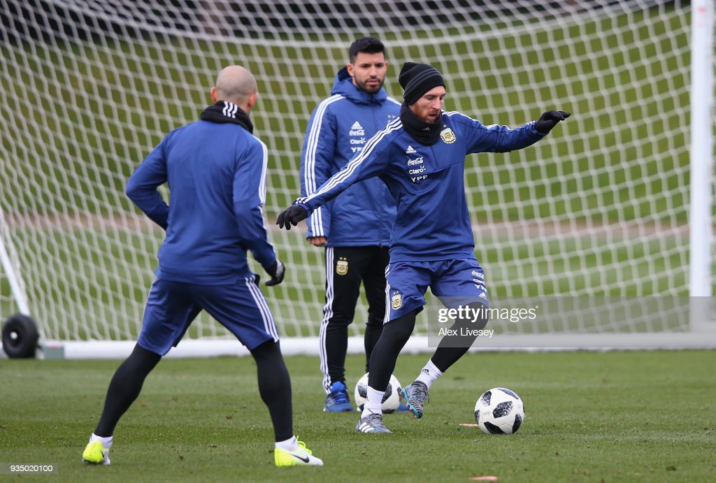 Lionel Messi of Argentina controls the ball as Javier Mascherano and Sergio Aguero look on during a Argentina training session at Manchester City Football Academy on March 20, 2018 in Manchester, England.