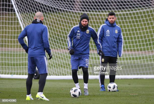 Lionel Messi of Argentina controls the ball as Javier Mascherano and Sergio Aguero look on during a Argentina training session at Manchester City...