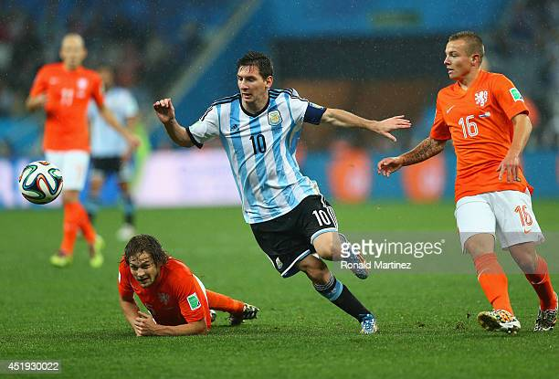 Lionel Messi of Argentina controls the ball as Jordy Clasie of the Netherlands gives chase during the 2014 FIFA World Cup Brazil Semi Final match...