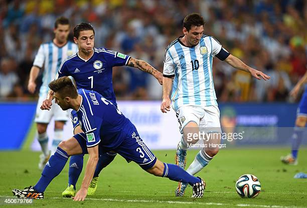 Lionel Messi of Argentina controls the ball on his way to scoring his team's second goal against Ermin Bicakcic and Muhamed Besic of Bosnia and...