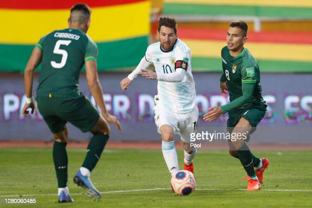 Lionel Messi of Argentina controls the ball past José María Carrasco of Bolivia and Boris Céspedes of Bolivia during a match between Bolivia and...