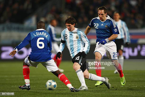 Lionel Messi of Argentina dribbles towards Lassana Diarra as Franck Ribery looks on during the International Friendly match between France and...