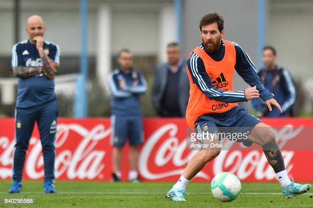 Lionel Messi of Argentina drives the ball as Jorge Sampaoli coach of Argentina looks on during a training session at 'Julio Humberto Grondona'...