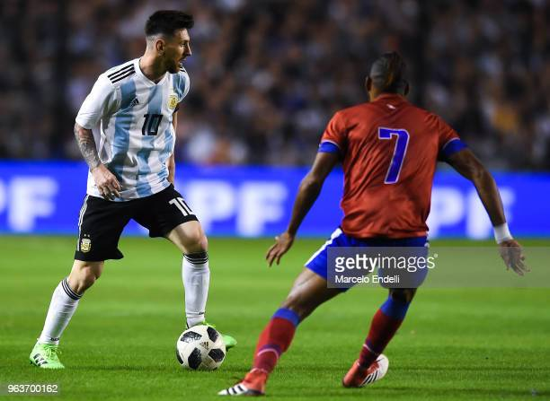 Lionel Messi of Argentina drives the ball while Fabien Vorbe of Haiti defends during an international friendly match between Argentina and Haiti at...