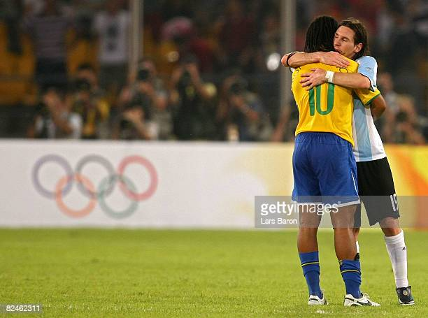 Lionel Messi of Argentina embraces Ronaldinho of Brazil after the men's football semifinal match between Argentina and Brazil at Workers' Stadium on...