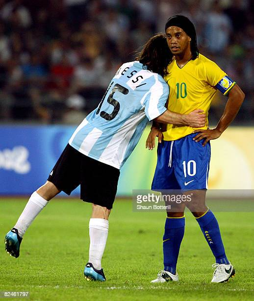 Lionel Messi of Argentina embraces Ronaldinho of Brazil during the men's football semifinal match between Argentina and Brazil at Workers' Stadium on...