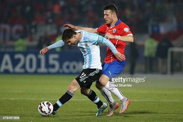 Lionel Messi of Argentina fights for the ball with Angelo Enriquez of Chile during the 2015 Copa America Chile Final match between Chile and...