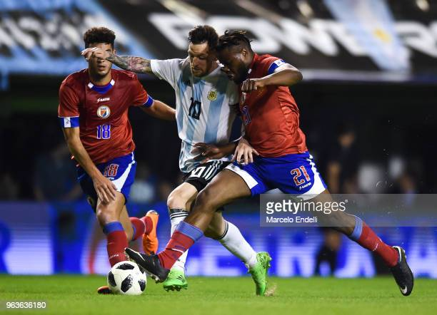 Lionel Messi of Argentina fights for the ball with Bryan Chevreruil of Haiti during an international friendly match between Argentina and Haiti at...
