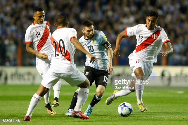 Lionel Messi of Argentina fights for the ball with Edison Flores of Peru and Renato Tapia of Peru during a match between Argentina and Peru as part...