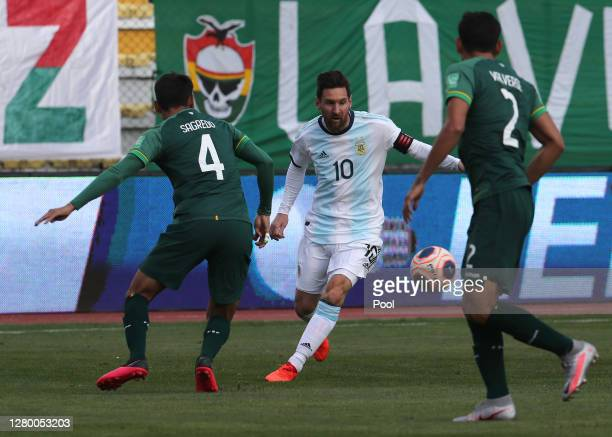 Lionel Messi of Argentina fights for the ball with José Sagredo and Gabriel Valverde of Bolivia during a match between Bolivia and Argentina as part...