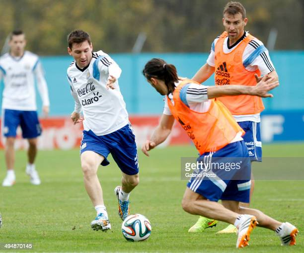 Lionel Messi of Argentina fights for the ball with Martin Demichelis as Hugo Campagnaro looks on during an Argentina training session at Ezeiza...