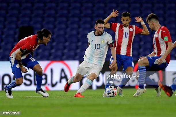 Lionel Messi of Argentina fights for the ball with Ángel Romero of Paraguay during a match between Argentina and Paraguay as part of South American...