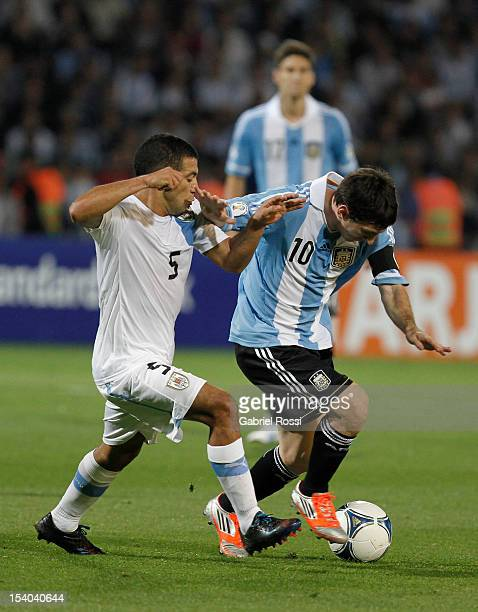 Lionel Messi of Argentina fights for the ball with Walter Gargano of Uruguay during a match between Argentina and Uruguay as part of the South...