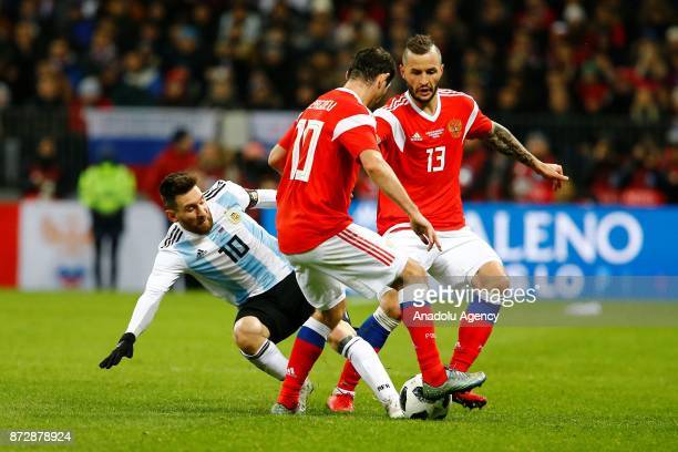 Lionel Messi of Argentina in action against Fedor Kudryashov and Alan Dzagoev of Russia during the international friendly match between Russia and...