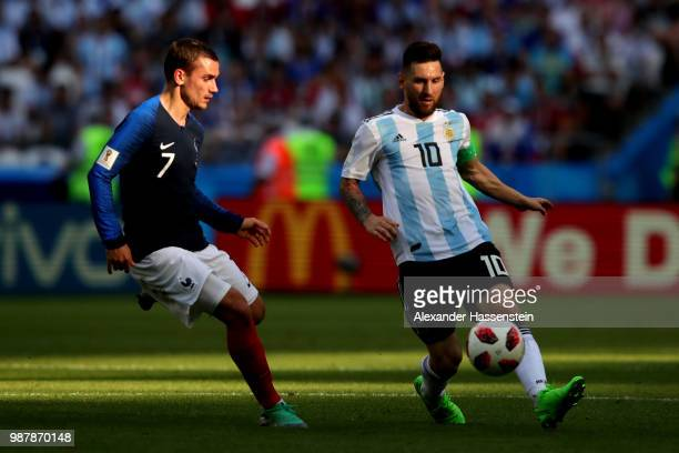 Lionel Messi of Argentina is challenged by Antoine Griezmann of France during the 2018 FIFA World Cup Russia Round of 16 match between France and...