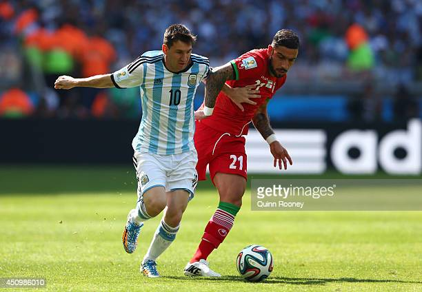 Lionel Messi of Argentina is challenged by Ashkan Dejagah of Iran during the 2014 FIFA World Cup Brazil Group F match between Argentina and Iran at...