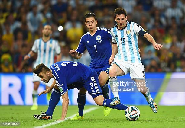 Lionel Messi of Argentina is challenged by Ermin Bicakcic of Bosnia and Herzegovina during the 2014 FIFA World Cup Brazil Group F match between...