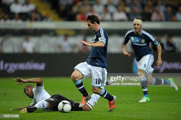 Lionel Messi of Argentina is challenged by Jerome Boateng of Germany during the international friendly match between Germany and Argentina and...