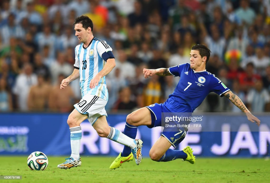 Lionel Messi of Argentina is challenged by Muhamed Besic of Bosnia and Herzegovina during the 2014 FIFA World Cup Brazil Group F match between Argentina and Bosnia-Herzegovina at Maracana on June 15, 2014 in Rio de Janeiro, Brazil.
