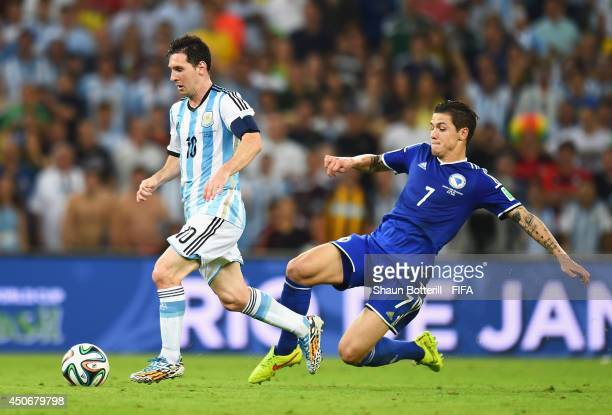 Lionel Messi of Argentina is challenged by Muhamed Besic of Bosnia and Herzegovina during the 2014 FIFA World Cup Brazil Group F match between...
