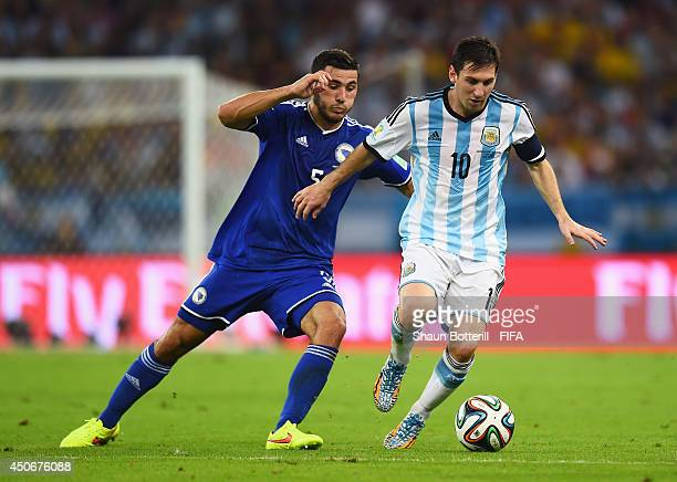 Lionel Messi of Argentina is chased by Sead Kolasinac of Bosnia and Herzegovina during the 2014 FIFA World Cup Brazil Group F match between Argentina...