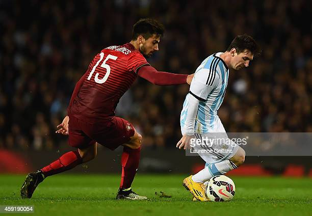 Lionel Messi of Argentina is closed down by Andre Gomes of Portugal during the International Friendly between Argentina and Portugal at Old Trafford...
