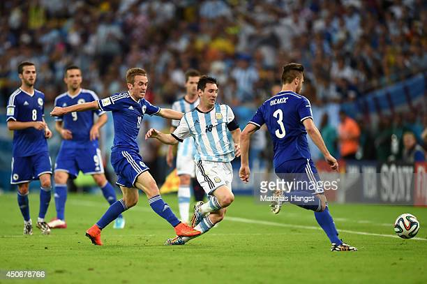 Lionel Messi of Argentina is fouled by Edin Visca of Bosnia and Herzegovina during the 2014 FIFA World Cup Brazil Group F match between Argentina and...