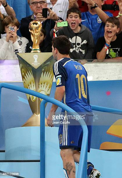 Lionel Messi of Argentina is passing by the trophy after the 2014 FIFA World Cup Brazil Final match between Germany and Argentina at Estadio Maracana...