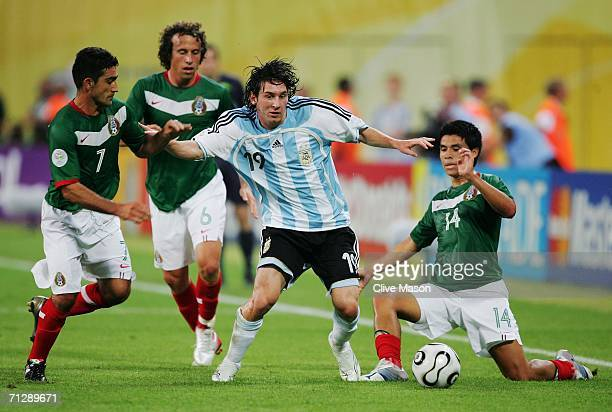 Lionel Messi of Argentina is put under pressure by Zinha Gerardo Torrado and Gonzalo Pineda of Mexico during the FIFA World Cup Germany 2006 Round of...