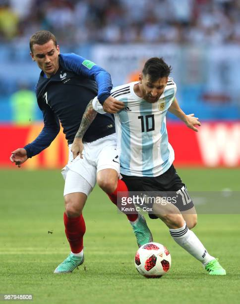 Lionel Messi of Argentina is tackled by Antoine Griezmann of France during the 2018 FIFA World Cup Russia Round of 16 match between France and...