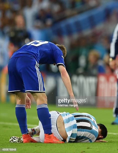 Lionel Messi of Argentina lies on the field as Edin Visca of Bosnia and Herzegovina stands over him after a foul during the 2014 FIFA World Cup...