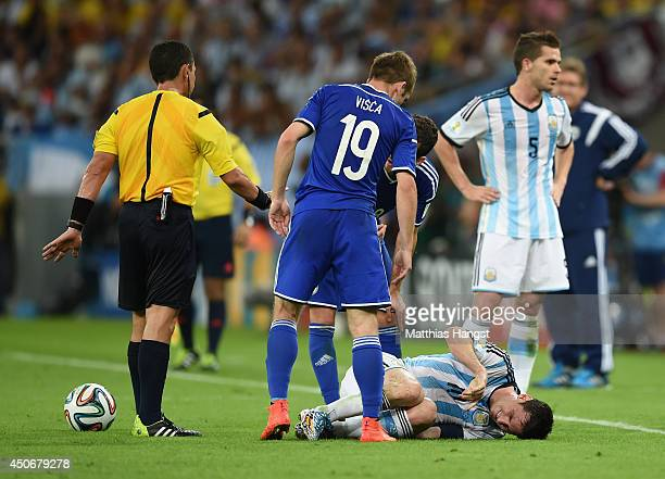 Lionel Messi of Argentina lies on the field as Edin Visca of Bosnia and Herzegovina and referee Joel Aguilar stand over him after a foul during the...