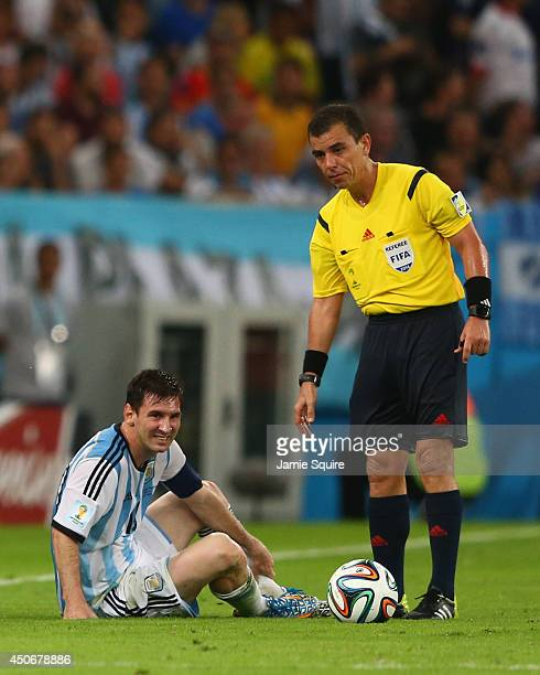 Lionel Messi of Argentina lies on the field as referee Joel Aguilar stands over him after a foul during the 2014 FIFA World Cup Brazil Group F match...