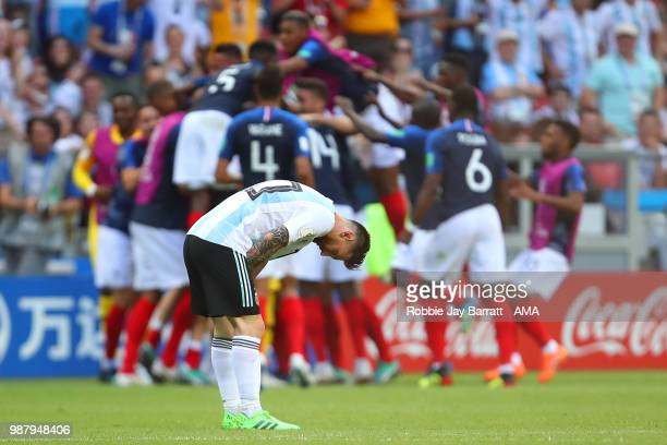 Lionel Messi of Argentina looks dejected as Benjamin Pavard of France celebrates with his team-mates after scoring a goal to make it 2-2 during the...