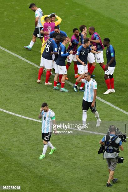 Lionel Messi of Argentina looks dejected following his sides defeat as France players celebrate following their sides victory in the 2018 FIFA World...