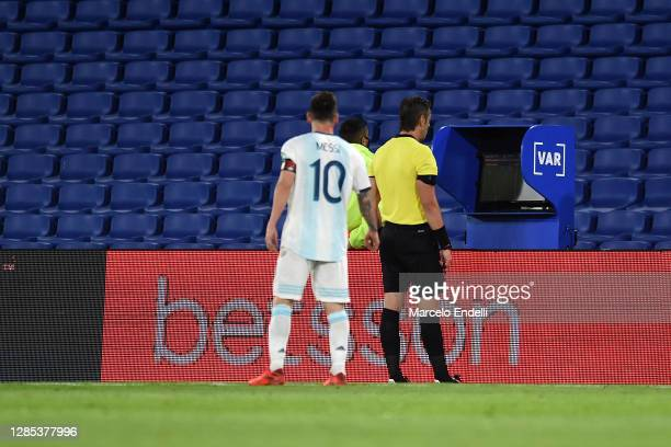 Lionel Messi of Argentina looks on as referee Raphael Claus checks the VAR to review a play during a match between Argentina and Paraguay as part of...