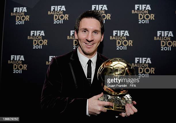 Lionel Messi of Argentina poses with the trophy after winning his third consecutive FIFA Ballon d'Or title at the FIFA Ballon d'Or Gala 2011 at the...