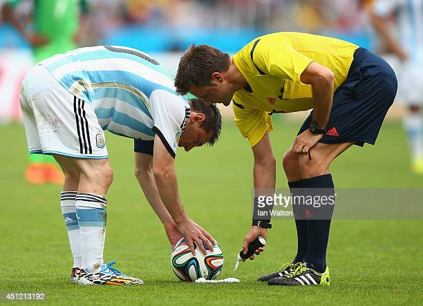Lionel Messi of Argentina prepares to take a free kick as referee Nicola Rizzoli sprays a temporary line during the 2014 FIFA World Cup Brazil Group...