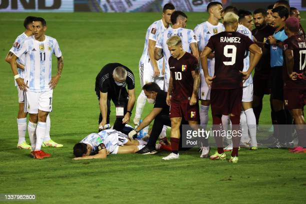 Lionel Messi of Argentina receives medical attention after being fouled as players of Argentina and Venezuela argue with Referee Leodán González...