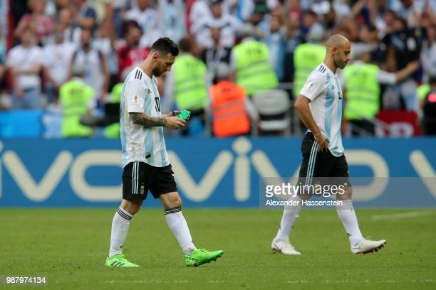 Lionel Messi of Argentina removes his captain's armband and looks dejected following the 2018 FIFA World Cup Russia Round of 16 match between France...