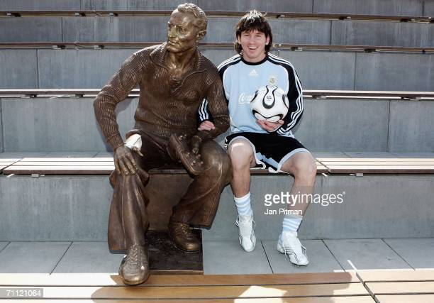 Lionel Messi of Argentina sits next to a statue of Adidas founder Adi Dassler at the World of Sports Stadium on June 4 2006 in Herzogenaurach Germany