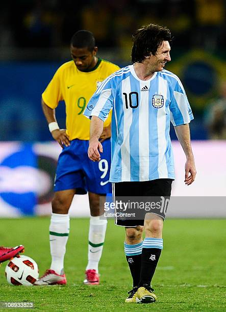Lionel Messi of Argentina smiles after scoring a goal, behind Robinho of Brazil observes the ball during their FIFA friendly match at Khalifa...