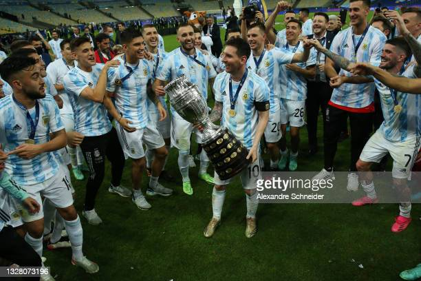 Lionel Messi of Argentina smiles with the trophy as he celebrates with teammates after winning the final of Copa America Brazil 2021 between Brazil...