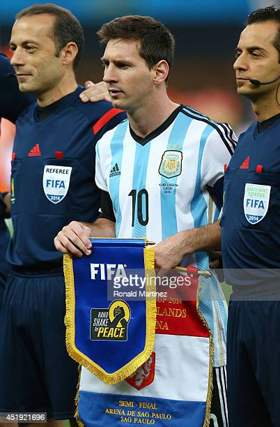 Lionel Messi of Argentina stands with officials prior to the 2014 FIFA World Cup Brazil Semi Final match between the Netherlands and Argentina at...