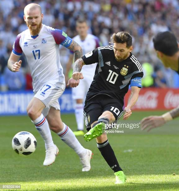 Lionel Messi of Argentina takes a shot near Aron Gunnarsson of Iceland during the first half of a football World Cup group stage match at Spartak...