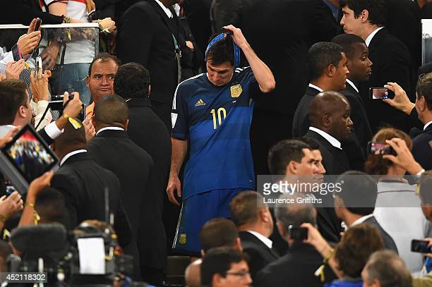Lionel Messi of Argentina takes his medal off after being defeated by Germany 10 during the 2014 FIFA World Cup Brazil Final match between Germany...
