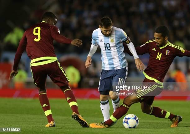 Lionel Messi of Argentina tries to dribble Sergio Cordova and Yangel Herrera R of Venezuela during a match between Argentina and Venezuela as part of...